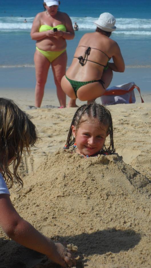 Ida blir begravd i sanden. (Observera snyggingarna i bakgrunden...)